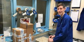 Adam packing brass CNC components during his placement with APT