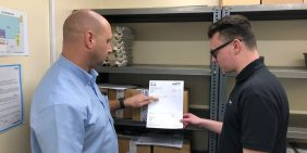 Apprentice Sam reviewing dispatch area paperwork with production manager Andy
